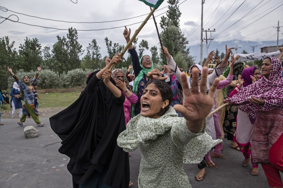 Women shout slogans as Indian policemen fire teargas and live ammunition in the air to stop a protes
