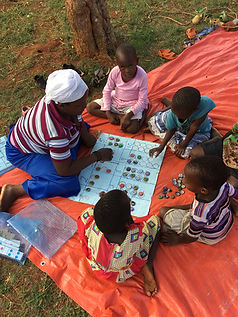 African woman teaches children to count while playing while sitting outside