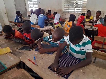 Un enfant lit le braille en classe au Sénégal