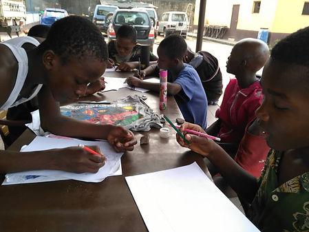 Des enfants dessinent à table