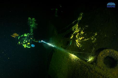 a diver lights up a wreck