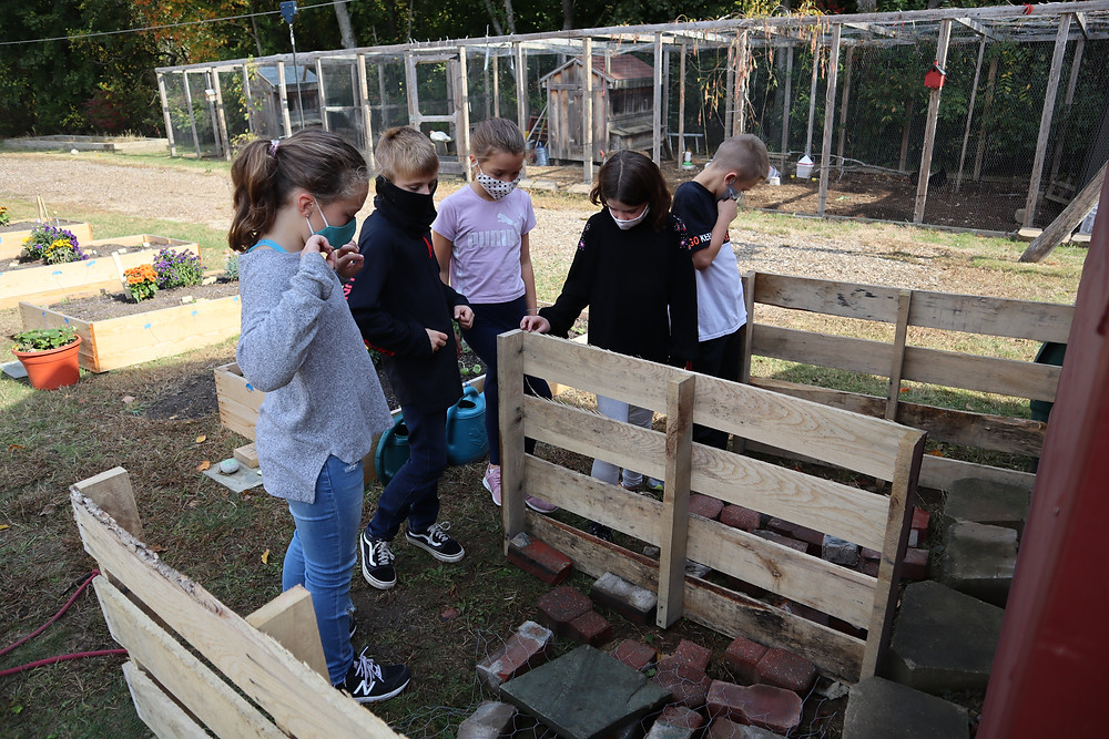 Five fourth and fifth graders contemplate pallets and figure out next steps to set up the composting structure.