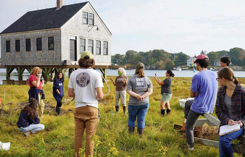 ten people stand in a cirlce on a grassy area in front of a house on stilts, having a discussion. In the background there is a lake.