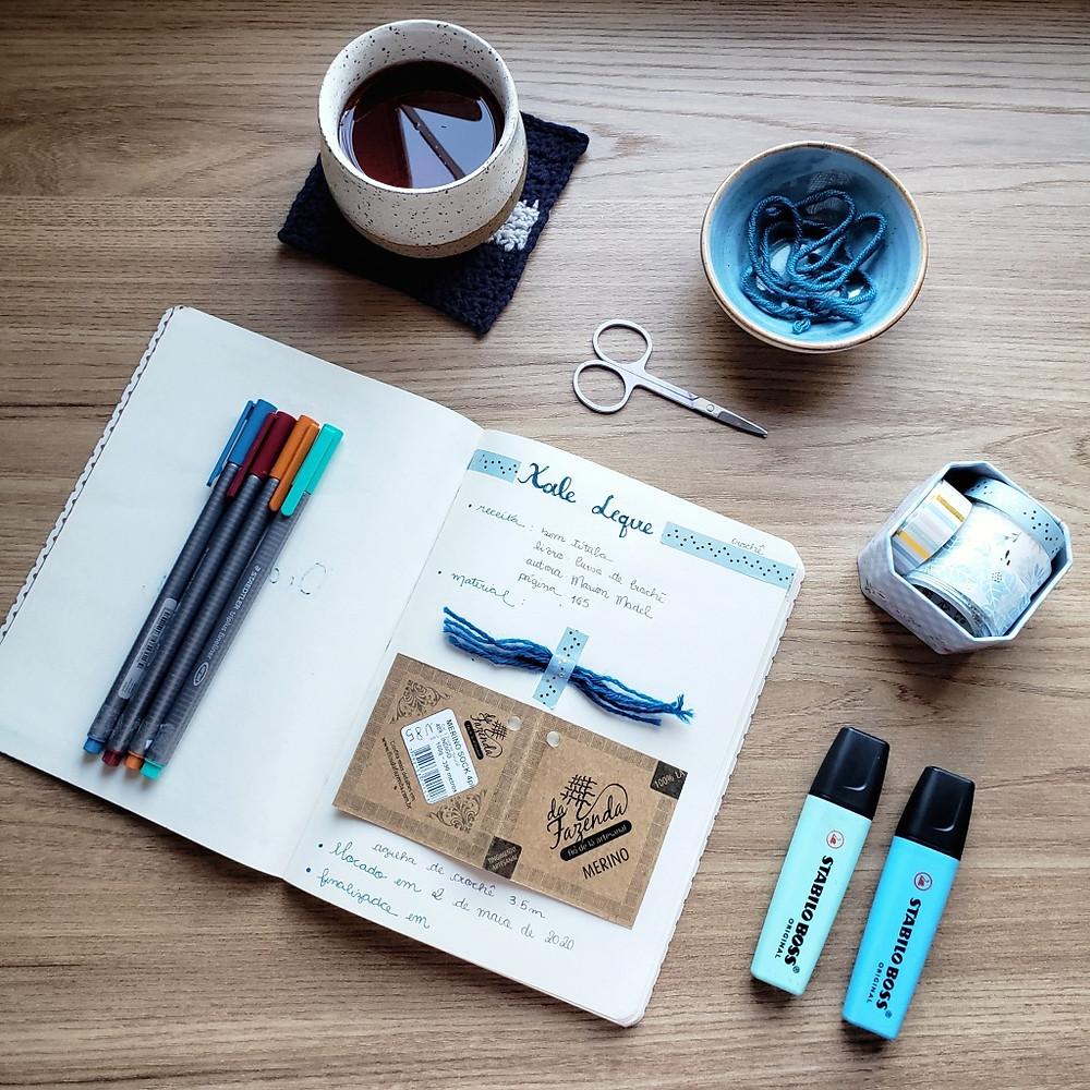 caderno, um diário têxtil com itens de papelaria, washi tapes, canetas e chá