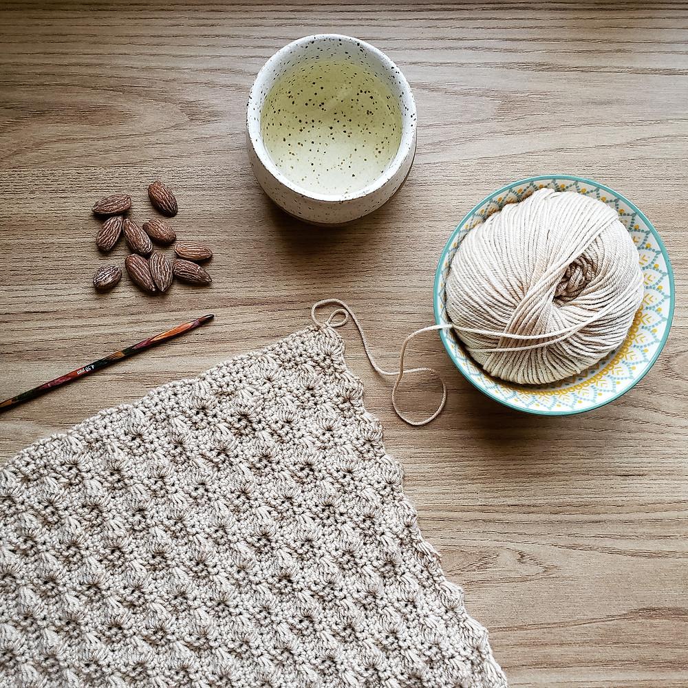 cachecol de crochê em ponto amêndoa com novelo e um copo de chá oriental