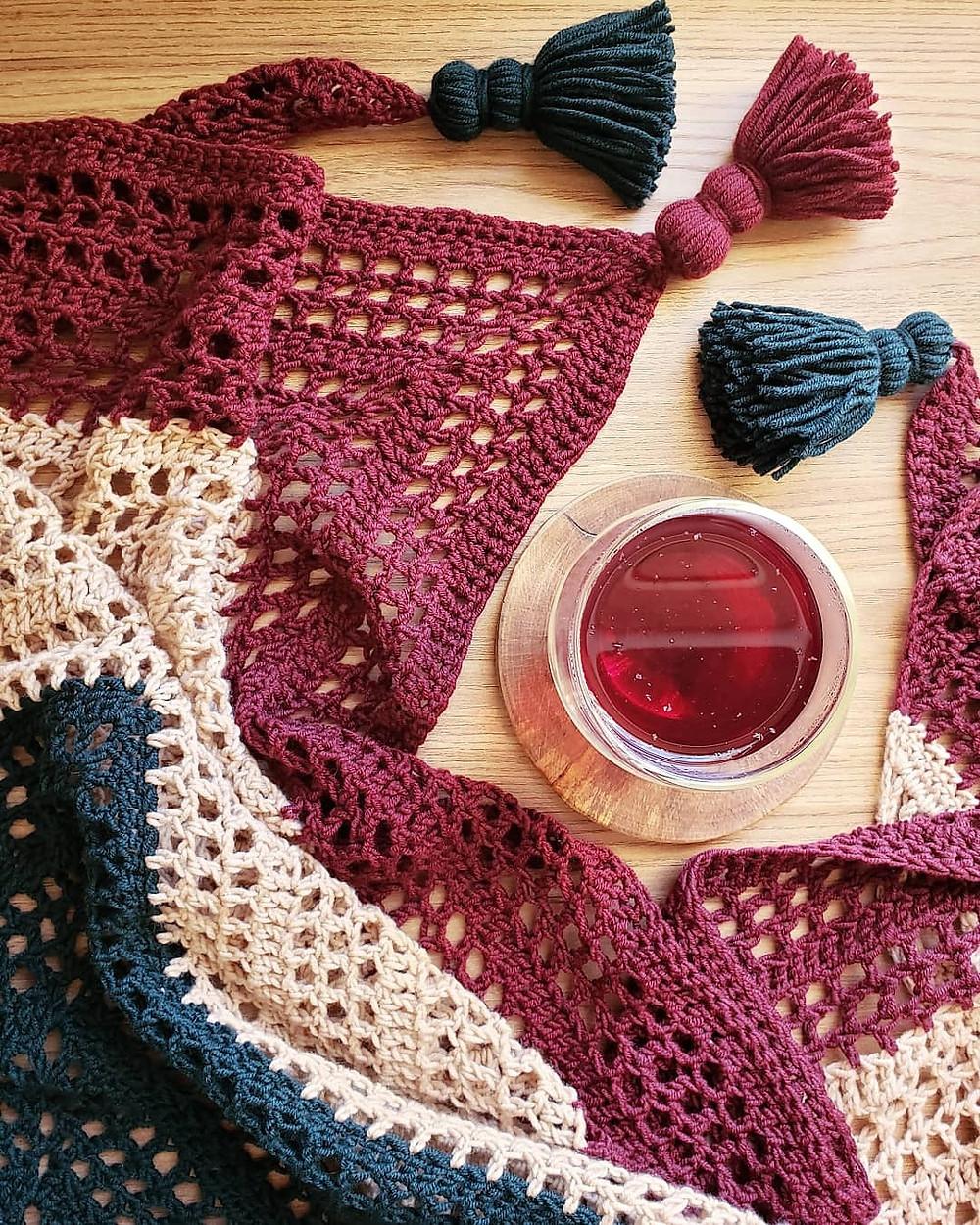 Xale de crochê em três cores e tassels com um copo de chá