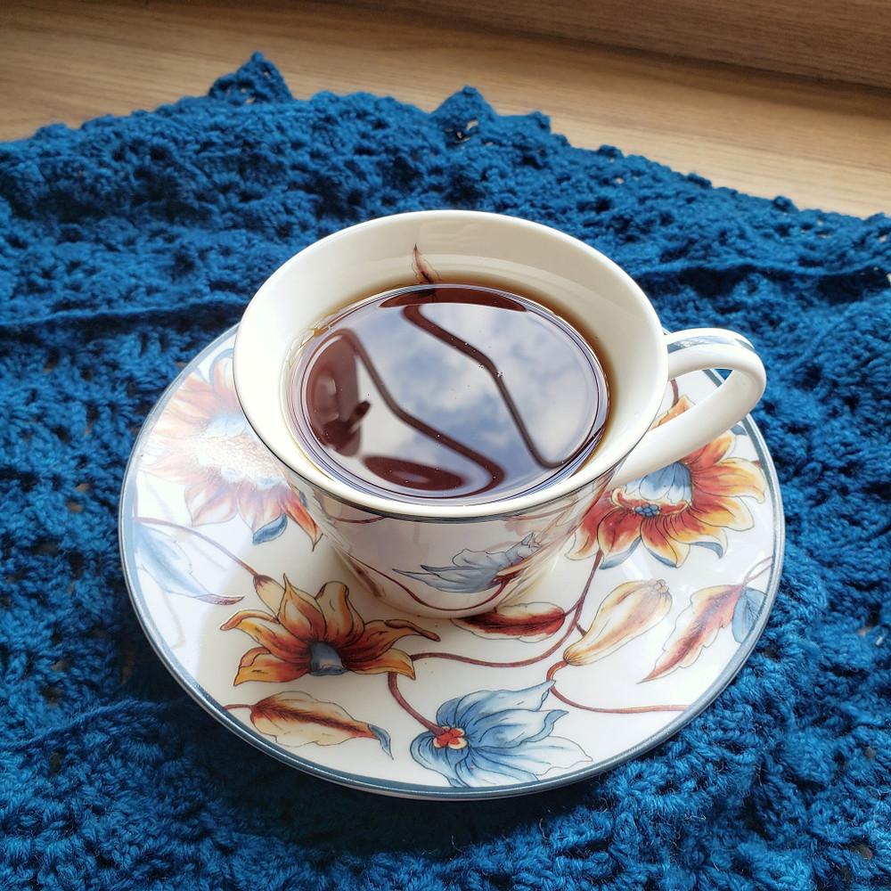 Uma xícara de chá aconchegante sobre um xale de crochê.