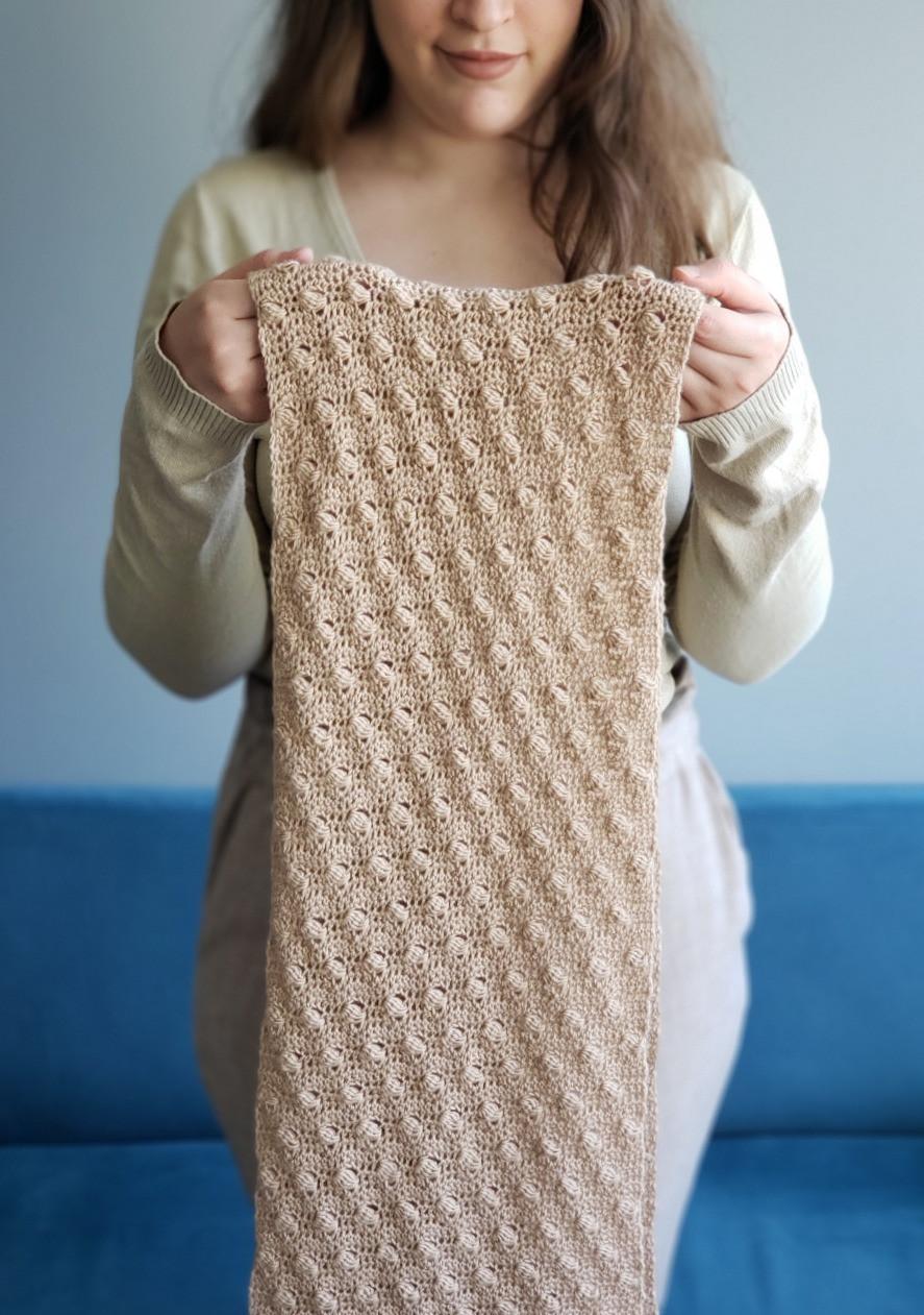 uma pessoa segura um cachecol de crochê com lã