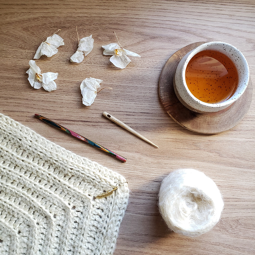 Xale de crochê pluma com novelo de lã mohair, agulha de crochê colorida, agulha de tapeçaria, copo de chá oriental e flores secas de orquídea,