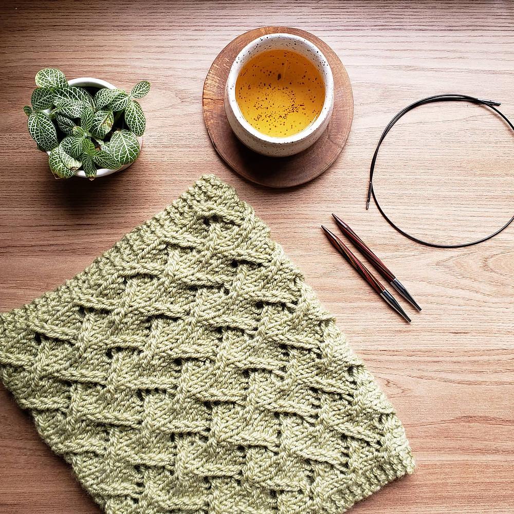 Cachecol de tricô rendado verde, agulhas intercambiaveis de tricô coloridas, copo de chá oriental e uma plantinha.