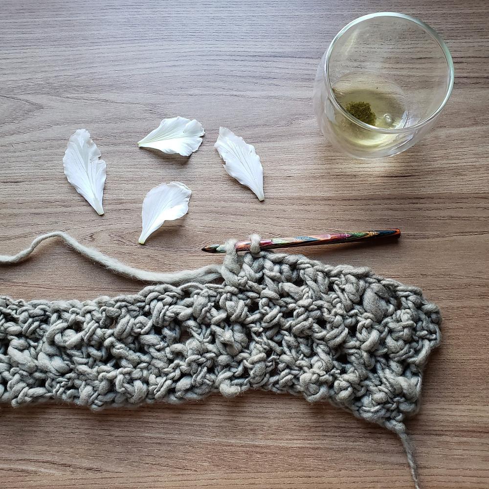 crochetando com lã natural e uma xícara de chá