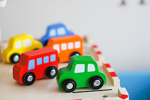 Green, Red, Orange, Blue, and Yellow wood toy cars on a wood platform.