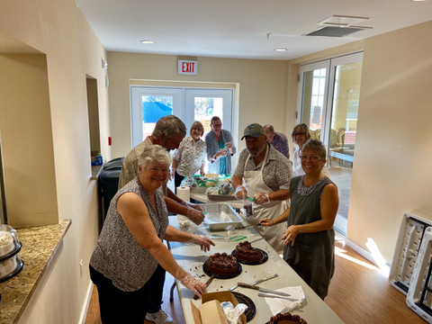 Volunteers cutting up cakes for the Community Thanksgiving Lunch