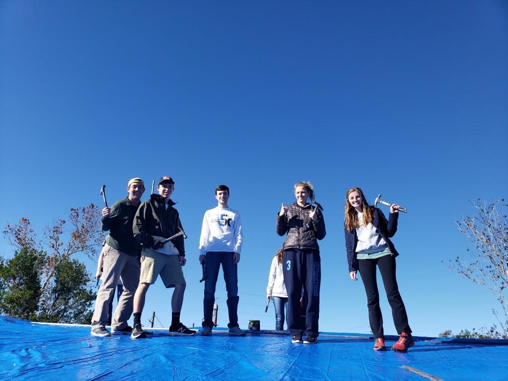 Students from Auburn University putting on new tarps!