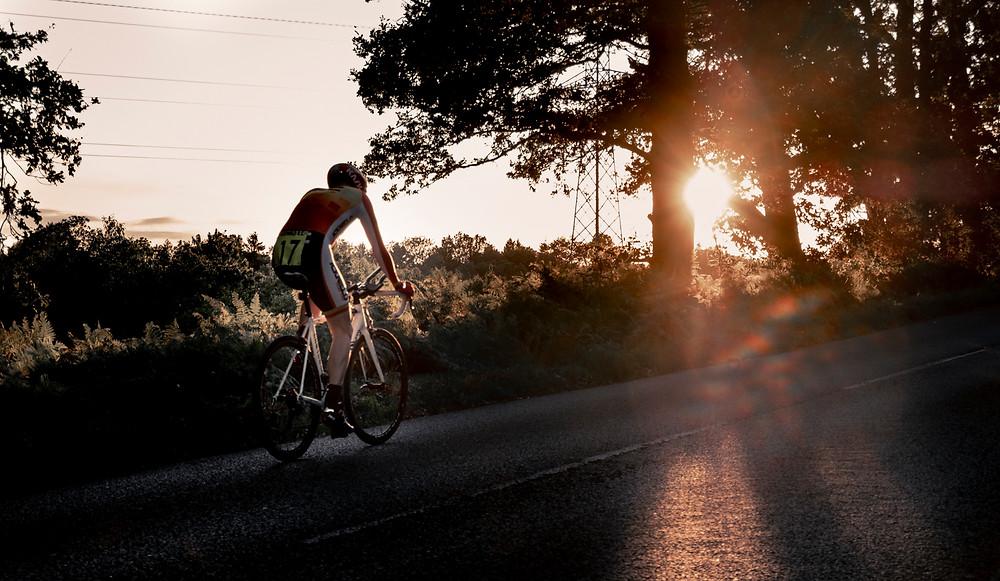 Cyclist riding into the sun set
