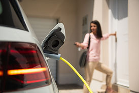 Close up of a electric car charger with female silhouette in the background, entering the