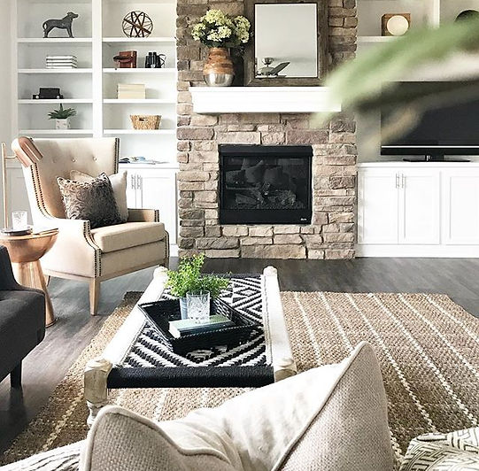 Decorated living room with stone fireplace and built in cabinets