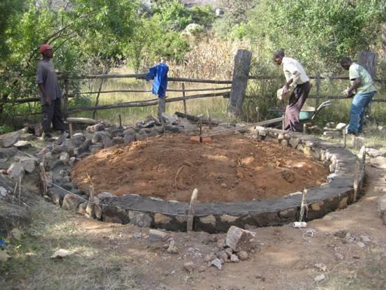 Kumbulani, Mr Mpofu and Diamond laying the stone foundations of the Staff Kitchen.