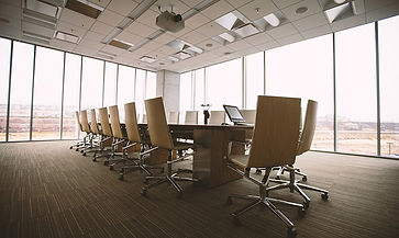Bright brownish office with business chairs and full height windows