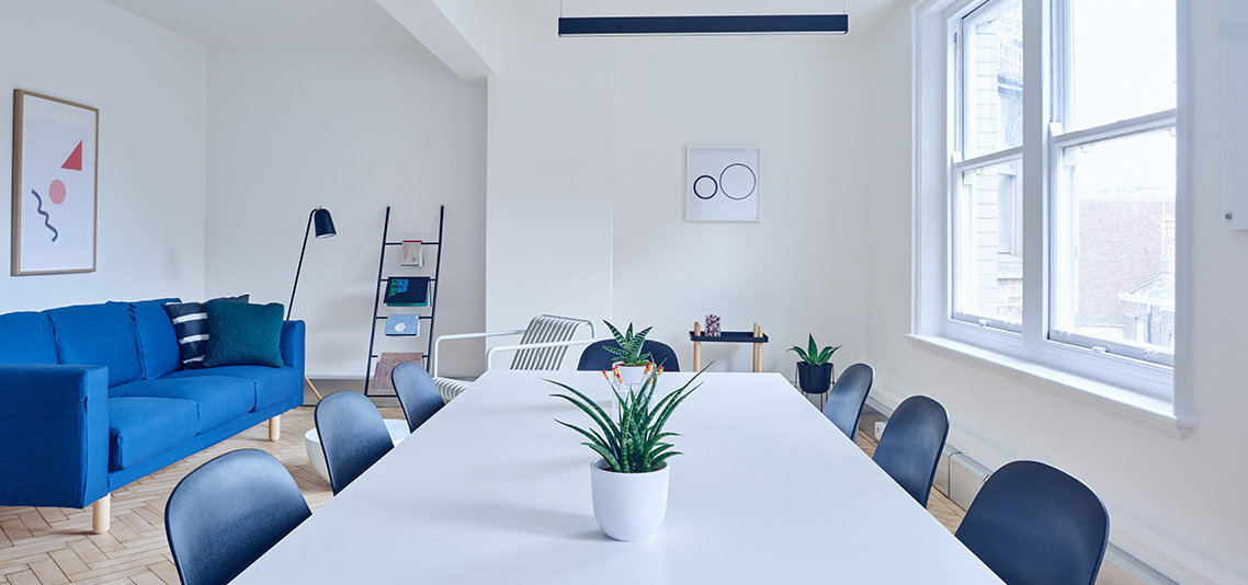 Bright white and blue gethering room with a jagged on the middle of the table