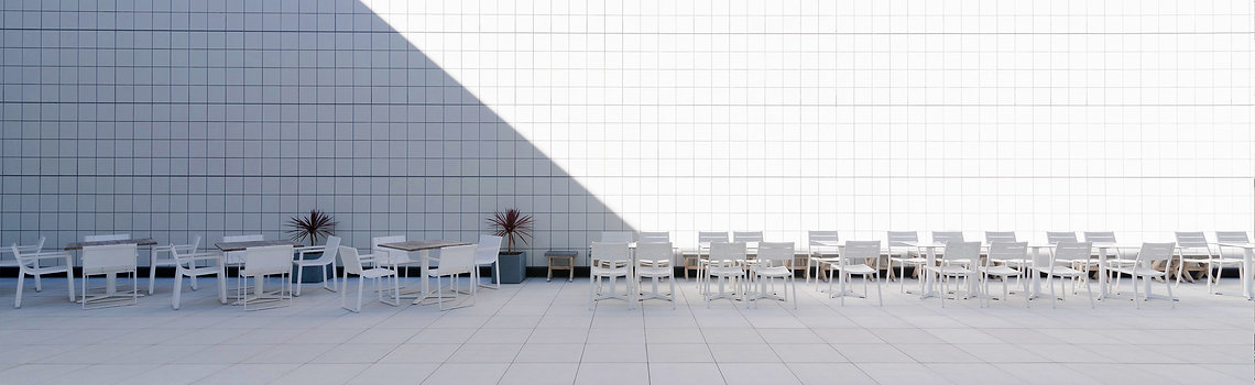 Chairs and tabes in a white balcony wth tile bricks on the floor and wall
