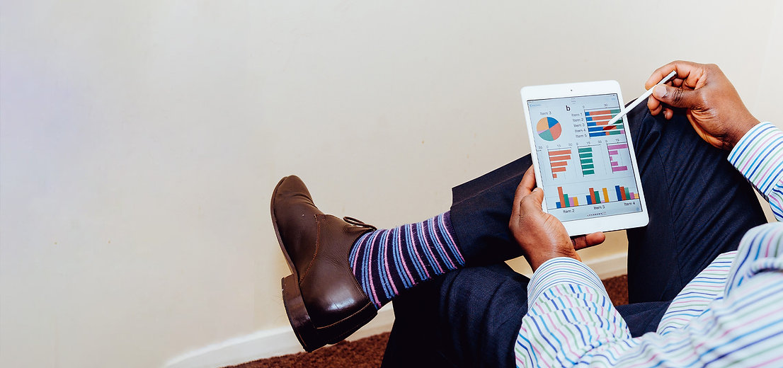 Man sitting and checking graphs on a tablet