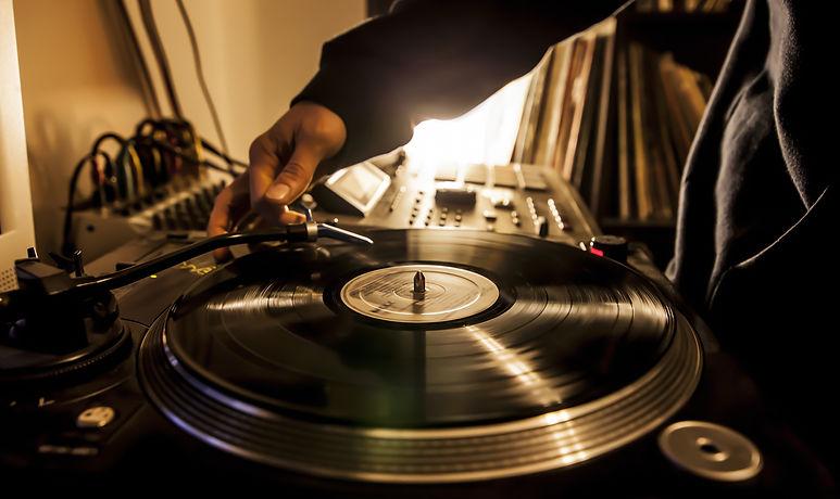 Dj in studio puts needle on record .jpg