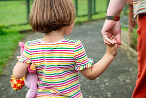 child-holds-hand-with-volunteer (1).jpg