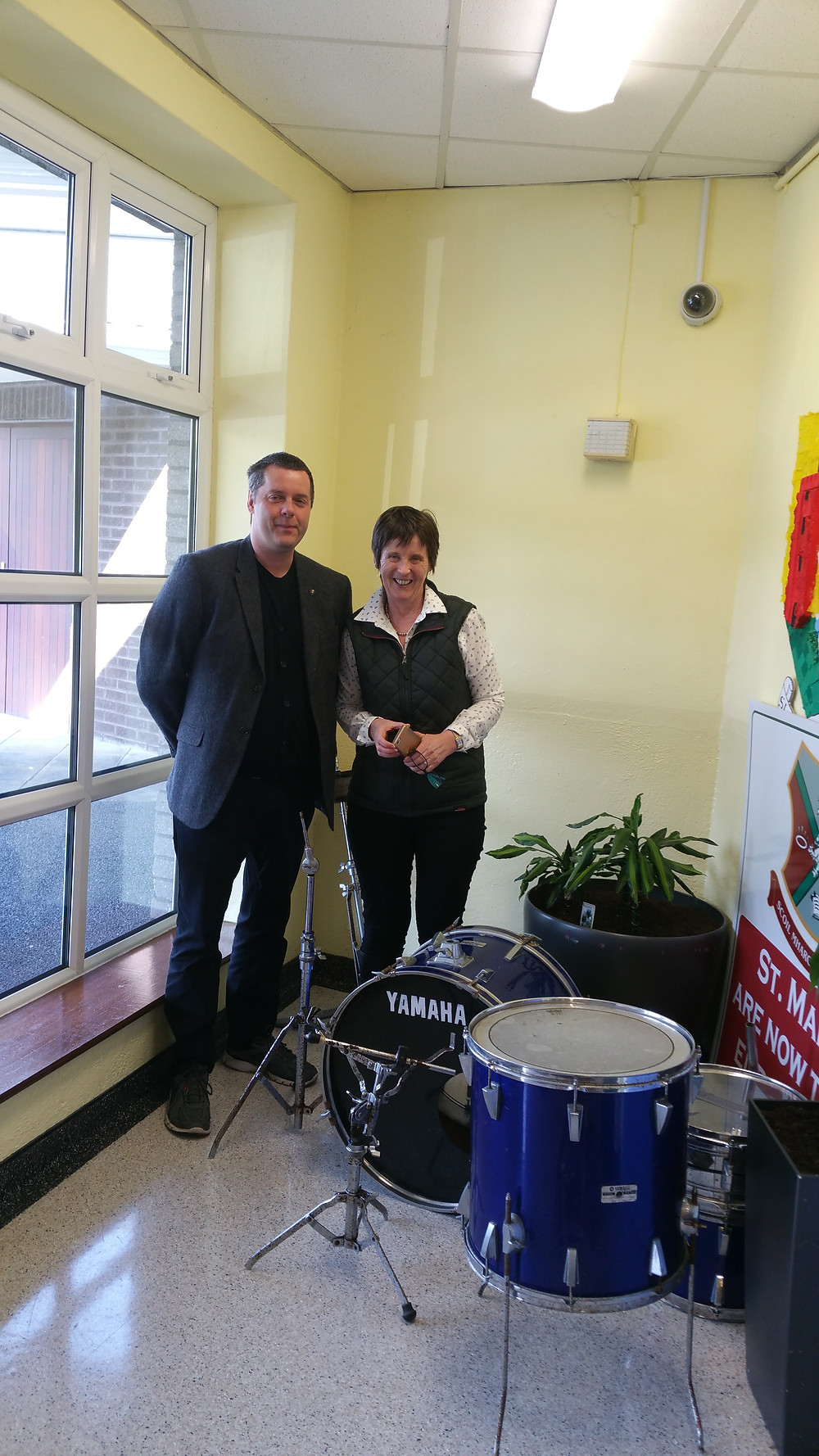 James Woods presenting his drum kit to Ms Coffey