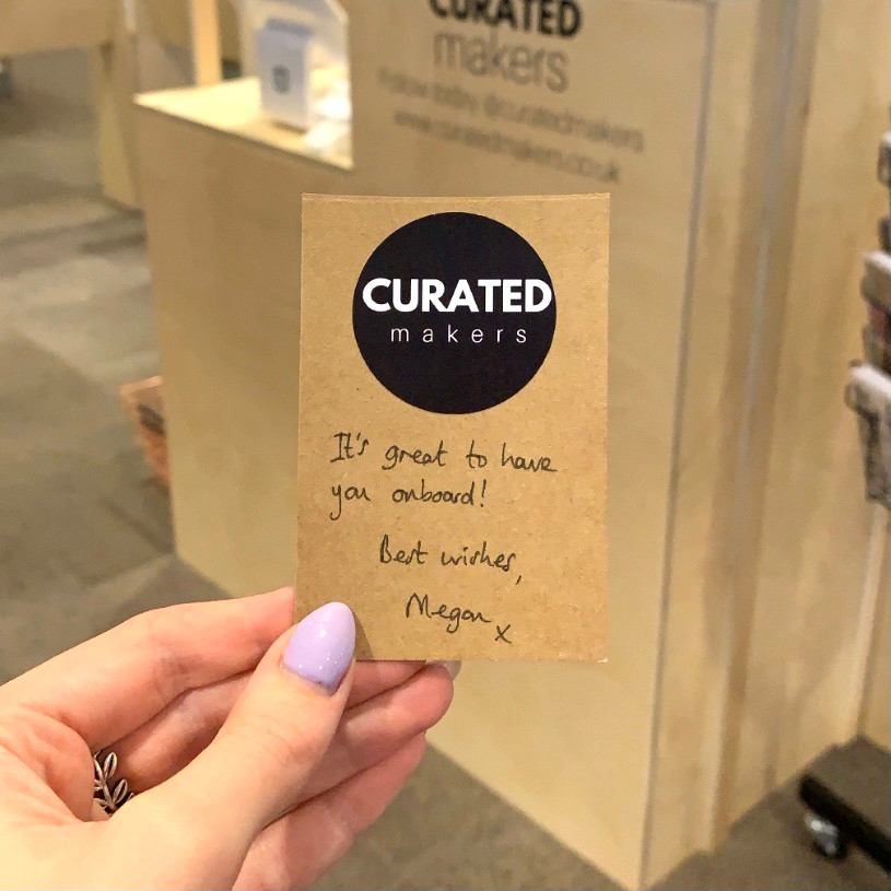 """A kraft Curated Markers business card saying """"It's great to have you on board! Best wishes Megan x"""""""