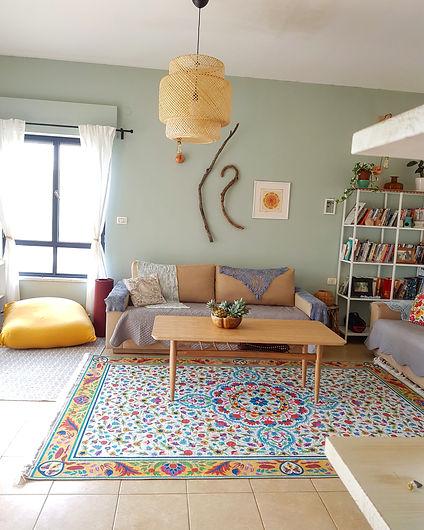 מצד אחד של הספה פינת מששחק נמוכה לילדים ומצידה השני ספרייה גבוהה.