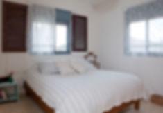 חדר שינה הורים. שילוב של תריסי עץ ישנים.