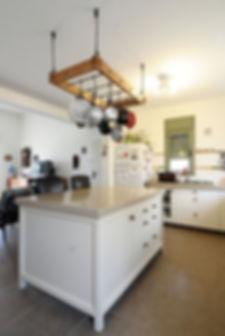 האי במטבח, מקום נהדר לבישול ואפייה. מעליו מתלה סירים מעץ גושני.