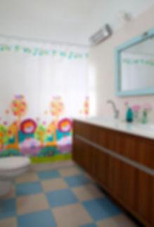 מבט אל חדר רחצה ילדים. רצפה שחמט צבעונית .