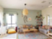 הסלון. ספות ששודרגו בעזרת כיסוי מיטה ומפות קרושה. שטיח צבעוני בדוגמה גיאומטרית ושולחן מעץ