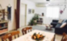 מבט מפינת האוכל אל הסלון. את הבית מקשטים עציצים ירוקים, עבודות מקרמה ורקמה.