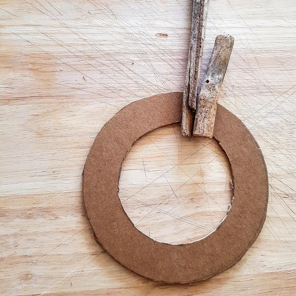 מדביקים את הענפים לטבעת הקרטון בעזרת דבק חם
