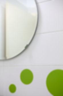 פרט בחדר הרחצה. מראה עגולה ודקורים עגולים בקרמיקה.