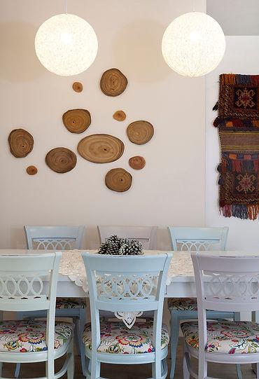 קישוט קיר בפינת האוכל, קומפוזיציה של פרוסות עץ. צילום הגר דופלט.