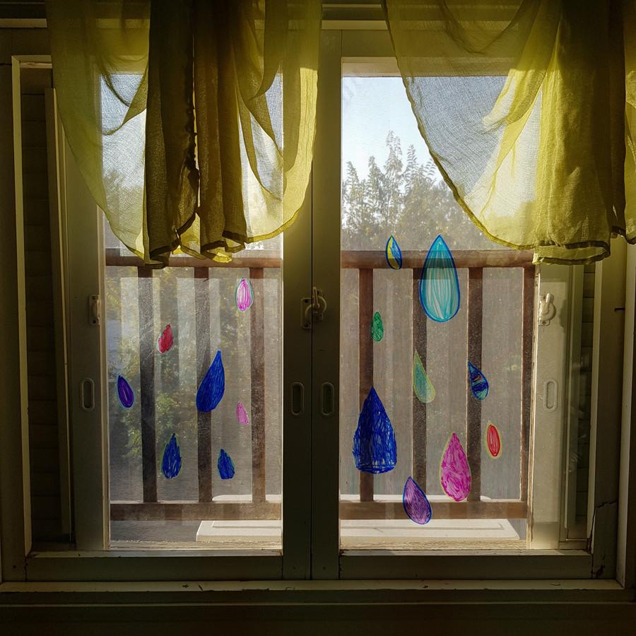 טיפות גשם משקפים צבועים מודבקות על החלון.