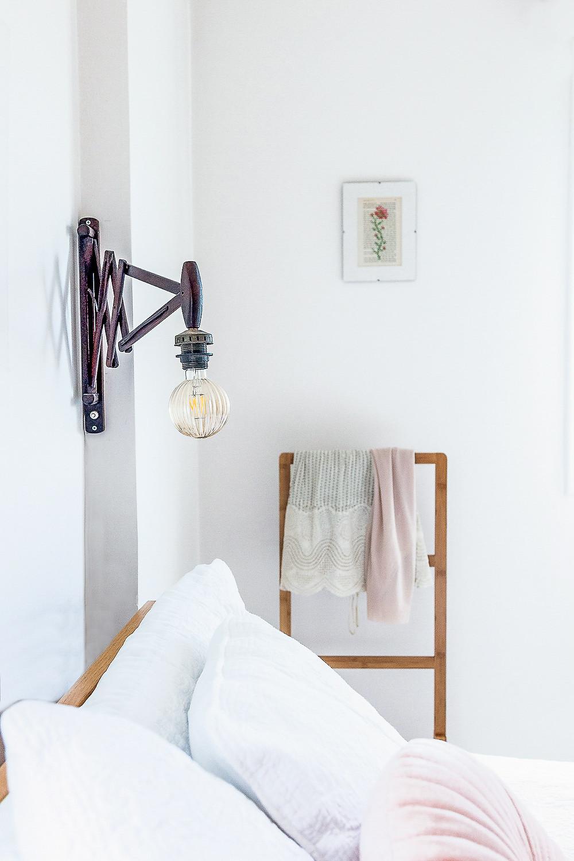 פרט בעיצובה של דקלה מנחם חדר שינה, מנורת קיר מיוחדת מעל מיטה מוצעת בלבן.