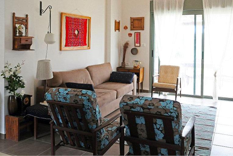 מבט אל הסלון. רהיטי וינטג' ואוספים על הקירות.