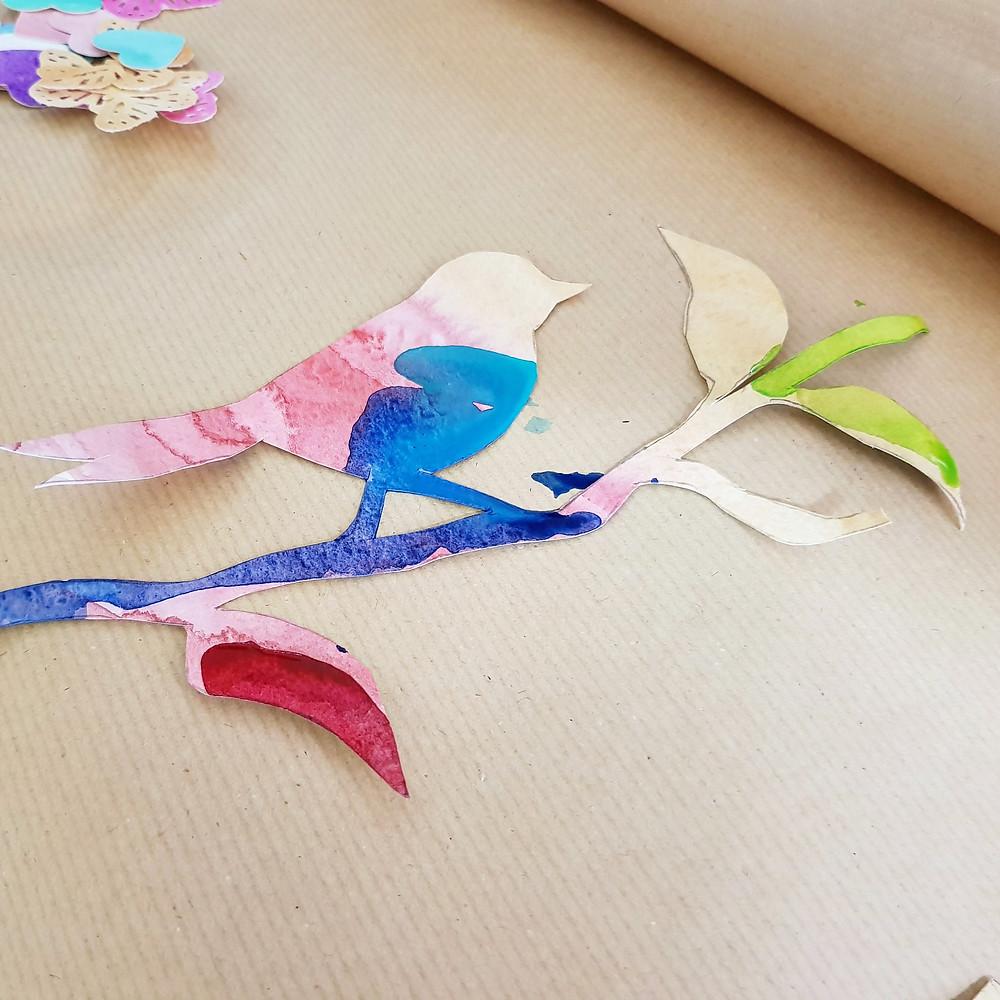דוגמת הציפור שנגזרה על רקע נייר קראפט חום.