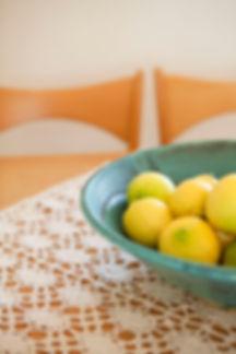 פרט לימונים בכלי קרמיקה ירקו על רקע מפת קרושה לבנה.