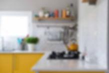 פינה במטבח, קרמיקה פסיפס אפורה ומדפים של בטון ועץ.