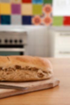 כיכר לחם שיצא מהתנור על רקע האריחים הצבעוניים.