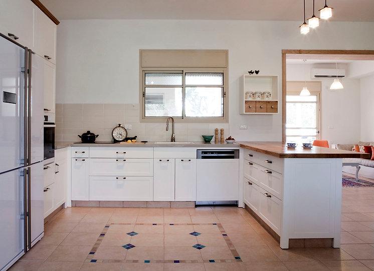 מבט אל המטבח מהכניסה לבית. מטבח לבן עם נגיעות עץ אלון ושטיח אריחים ברצפה.