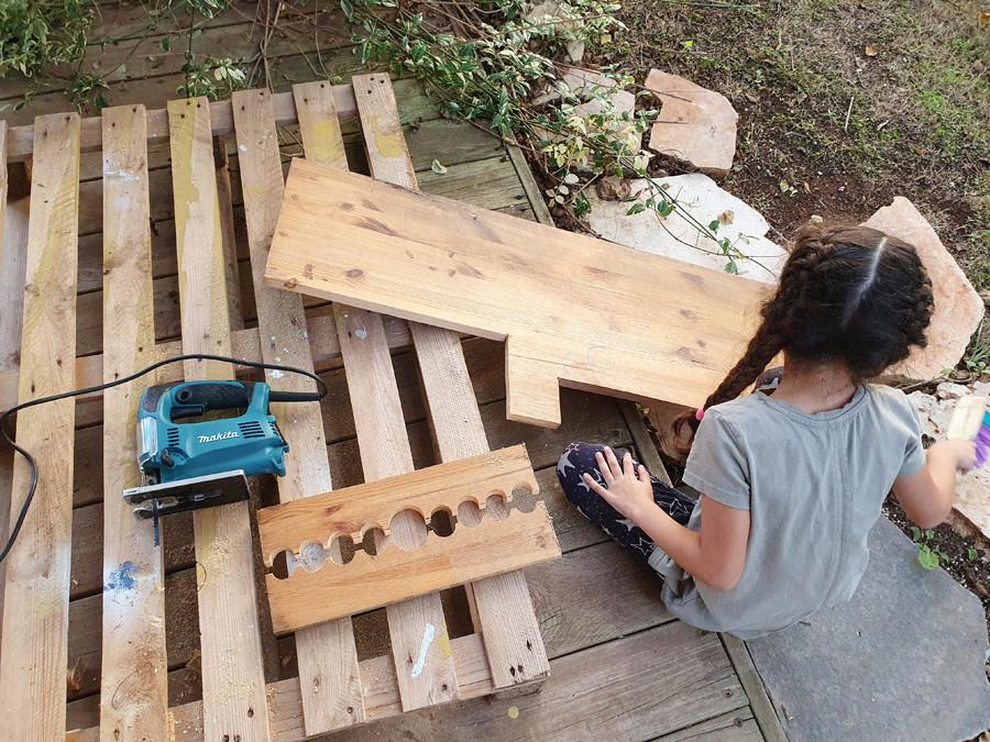 מבט על על פינת העבודה המאולתרת במרפסת שלנו. לוח העץ מונח על משטח עץ ומוכן לשיוף.