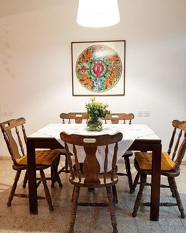פינת האוכל. שולחן וכסאות וינטג' מעץ, מפה לבנה, אהיל שפוט מאיקאה וצנצנת פרחים. ומעל השולחן ממוסגרת עבודת ריקמה של בעלת הבית