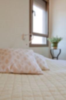 מבט אל המיטה ומאחוריה שידת צד משולחן עגול וגבוה.